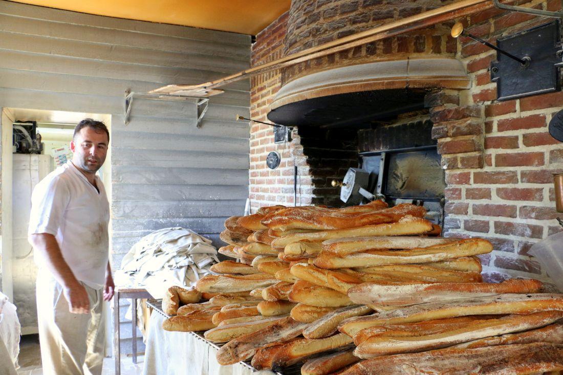 אנריק רובינו ליד תנור העצים וערימת הבגטים שלו