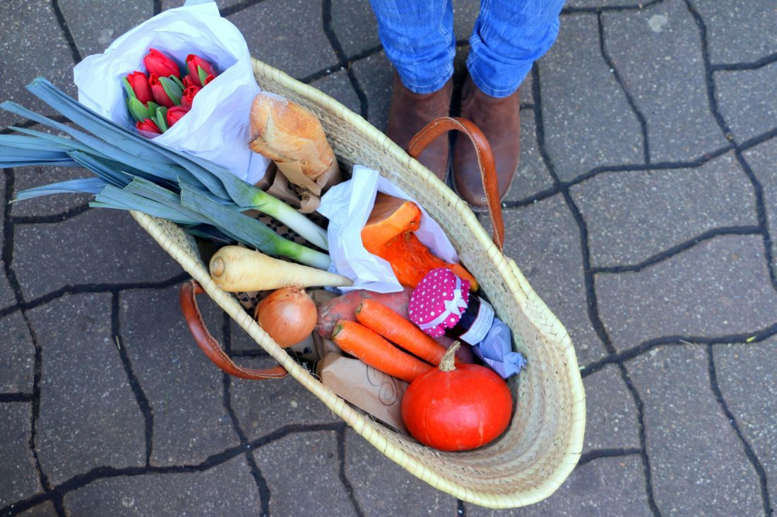 ירקות שורש נכנסים זה אחר זה לסל, בצל וכרישה מונחים לידם, וכמובן שגם פרחים