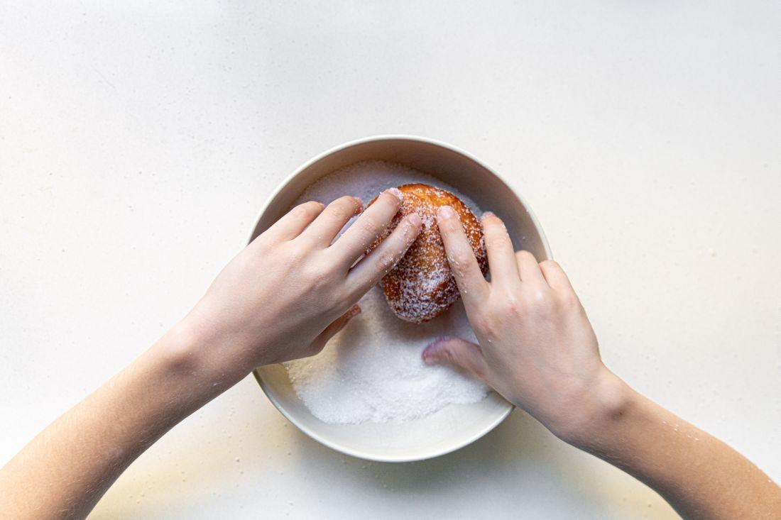 מגלגלים את הסופגניות בסוכר כשהן עדיין חמות