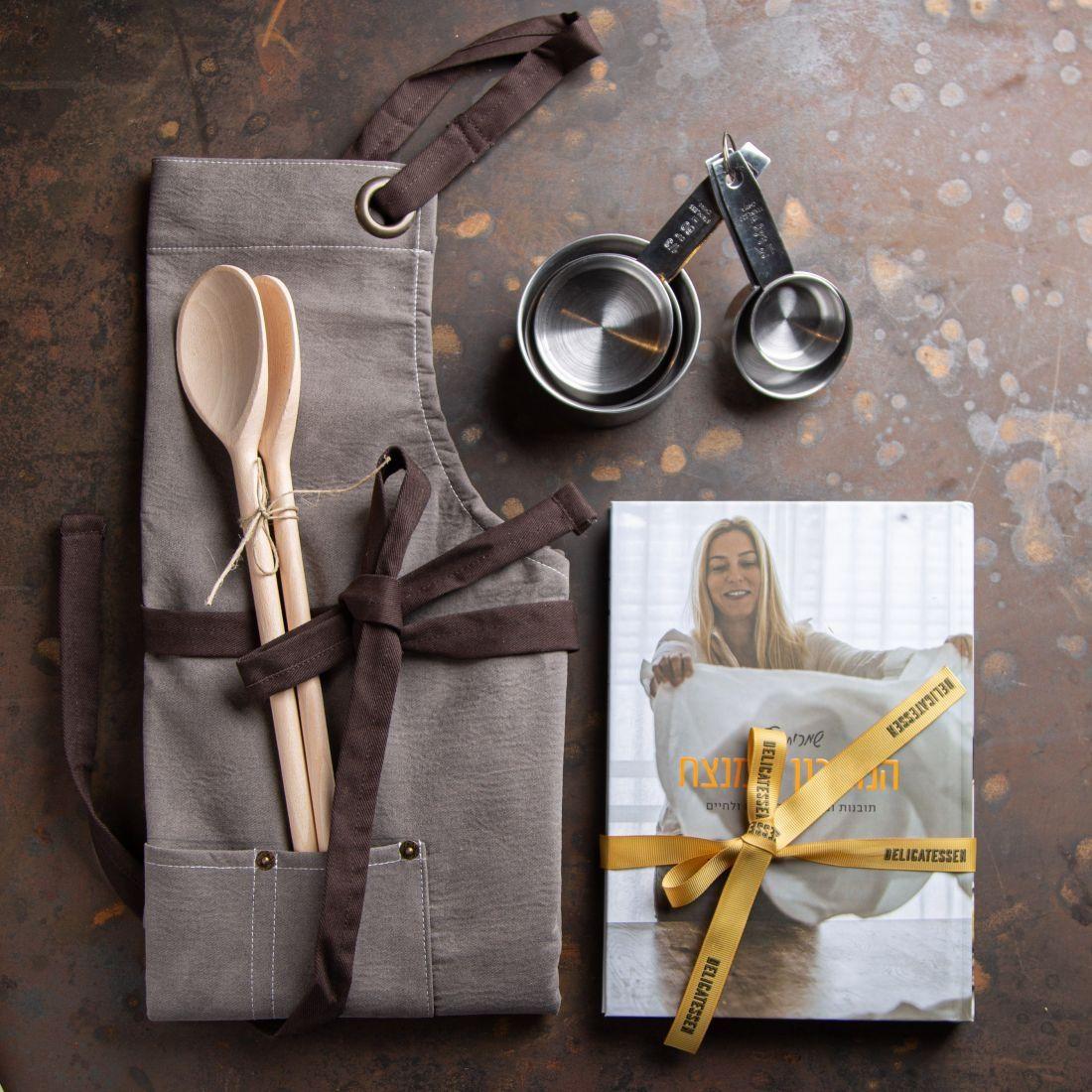 מארז כלים שלובים - מתנה לכל חובב בישול ובתוכה ספר ''המתכון המנצח'' של שמרית הילל מהתוכנית ''המטבח המנצח'', סינר דמוי עור לבישול וסט כוסות מידה.