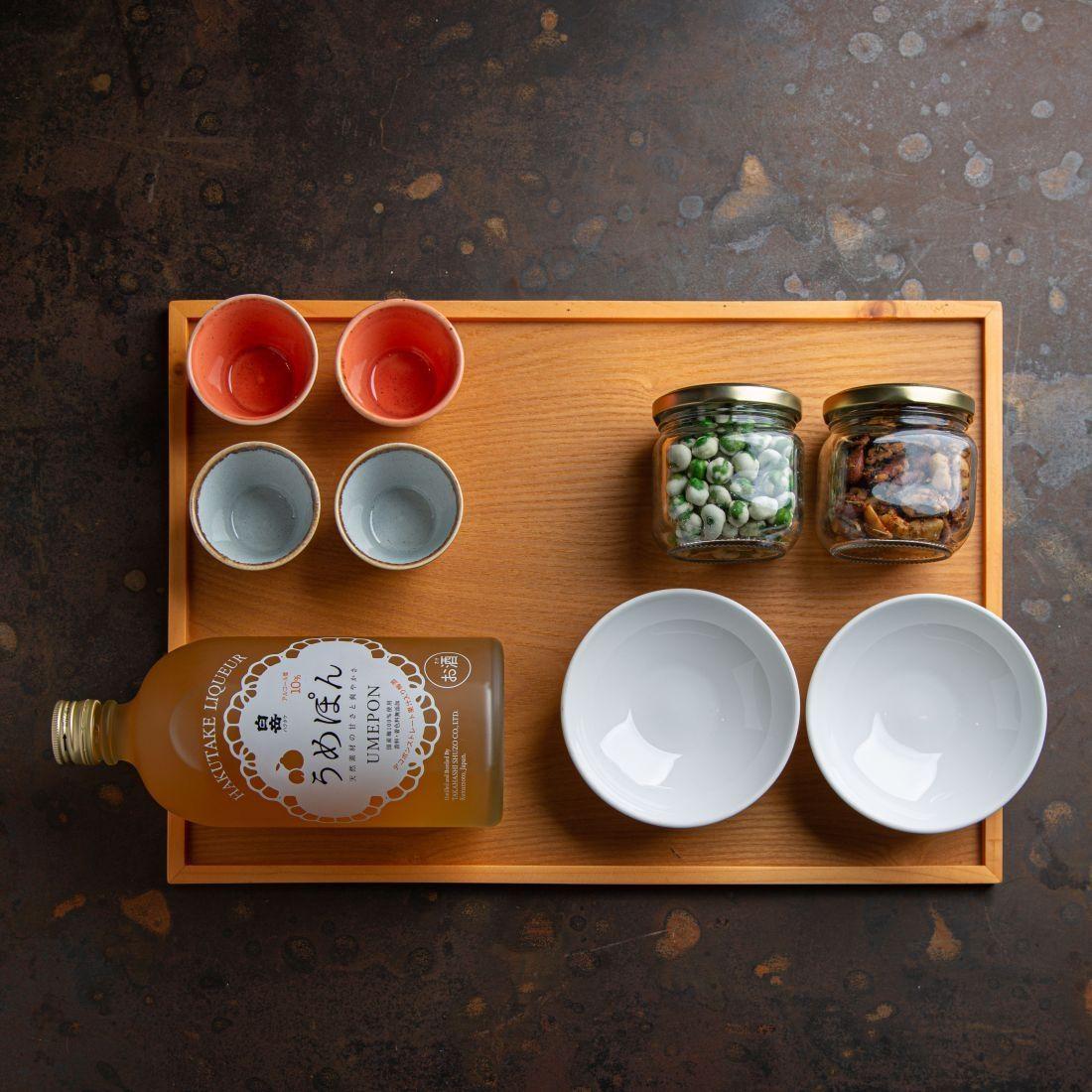 מארז דיסקו טוקיו - ליקר שזיפים יפני, 4 כוסות סאקה מקרמיקה, 2 קעריות זכוכית, אפונת וואסבי ואגוזי פולק לנשנוש.