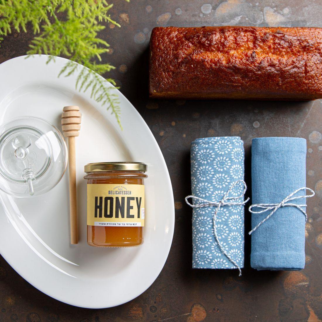 מארז הכל דבש - עוגה בחושה של הבייקרי, צלחת הגשה, דבש פרחי בר, רודה לדבש, כלי זכוכית לדבש וזוג מגבות מטבח.
