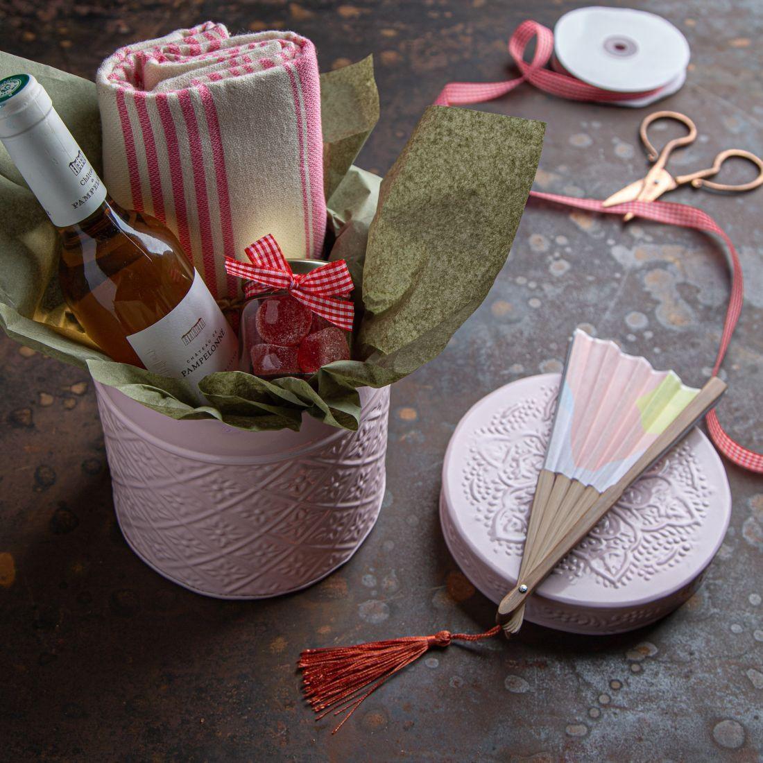 מארז החיים בורוד - קופסת פח ובפנים חצי בקבוק רוזה שאטו דה פמפלון, מניפה, מגבת חמאם וסוכריות גומי.