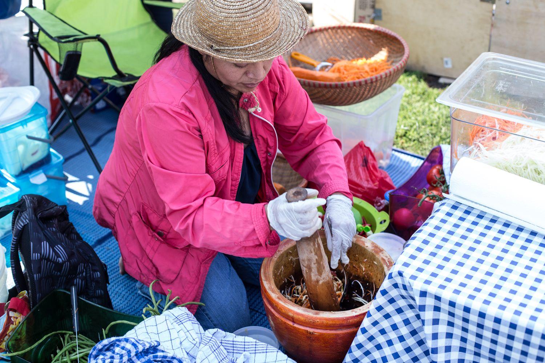 הגברת החביבה מכינה מנה אחר מנה של סלט הסום-טאם, סלט הפפאיה התיאלנדי