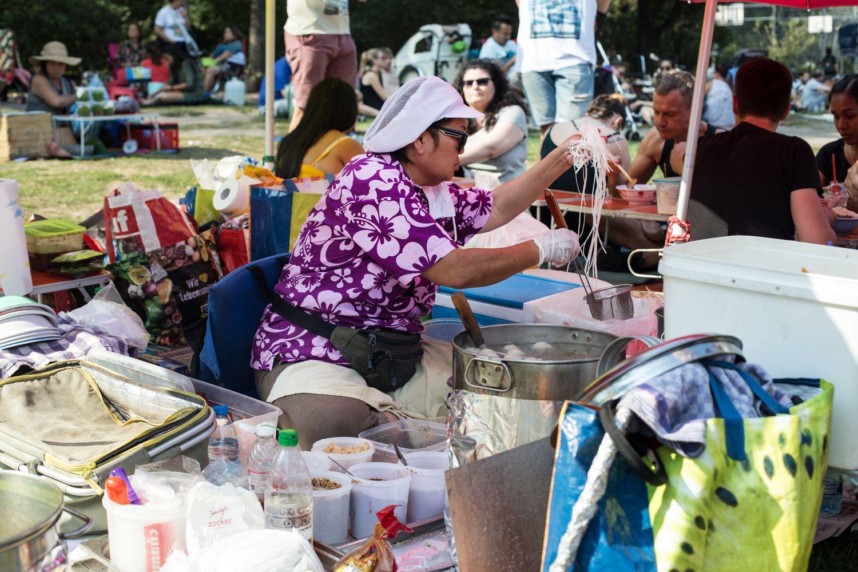 הגברת שמכינה מרק אטריות ונתחי חזיר בשוק התאילנדי