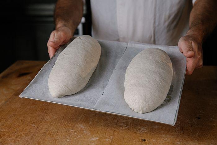 לעצב כל כדור לצורה של כיכר לחם ולהתפיח בחוץ כשעתיים על נייר אפייה