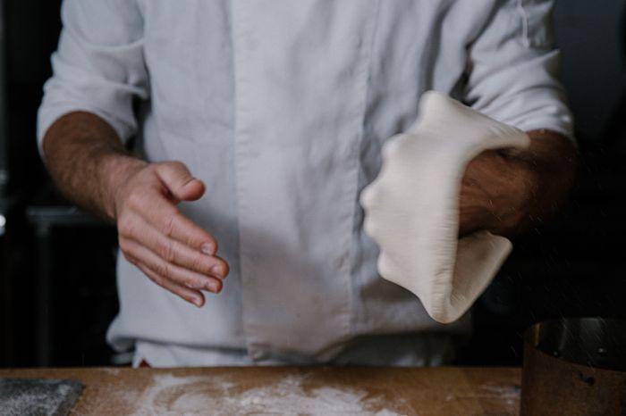 מתחילים למתוח את הבצק לפיצה עגולה יפה ודקה