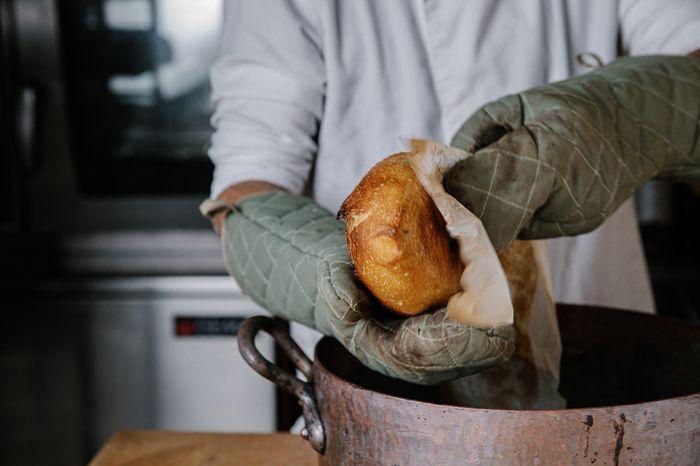 להכניס את הלחם בעזרת נייר האפייה לסיר החם, לחרוץ, לסגור את הסיר ולהכניס לתנור